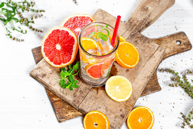 A glass of lemonade with ice cubes, sliced citrus and mint on old wooden boards