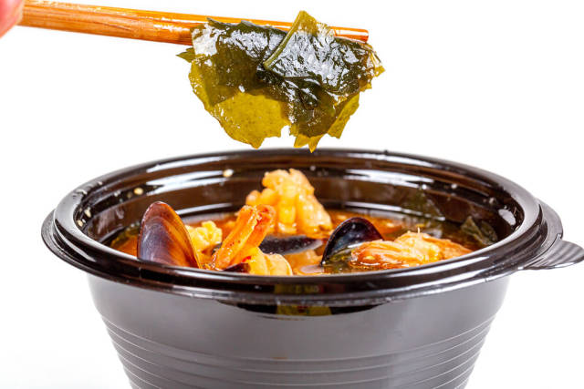 Wakame seaweed in wooden chopsticks and a bowl of miso soup
