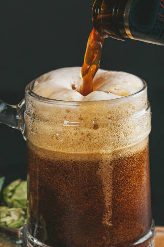 Cold dark beer is poured into a beer mug from a bottle