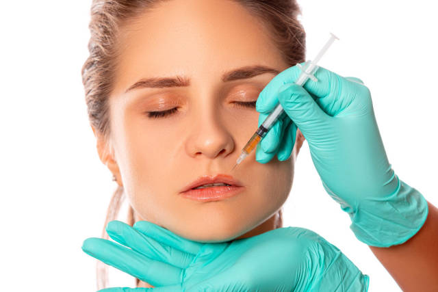 Womans face and doctors hands in gloves make an injection above the lip