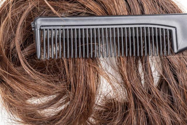 Close- up, black comb on dark female hair