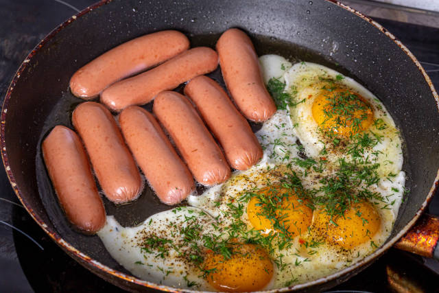 Sausages and fried eggs in a frying pan with spices and herbs