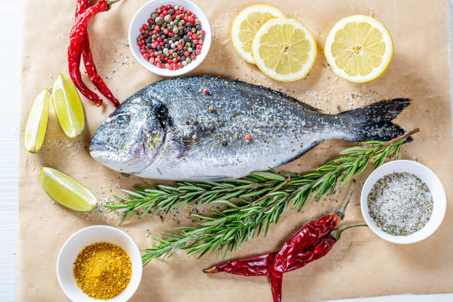 Dorado fish is prepared for baking on parchment paper with ingredients
