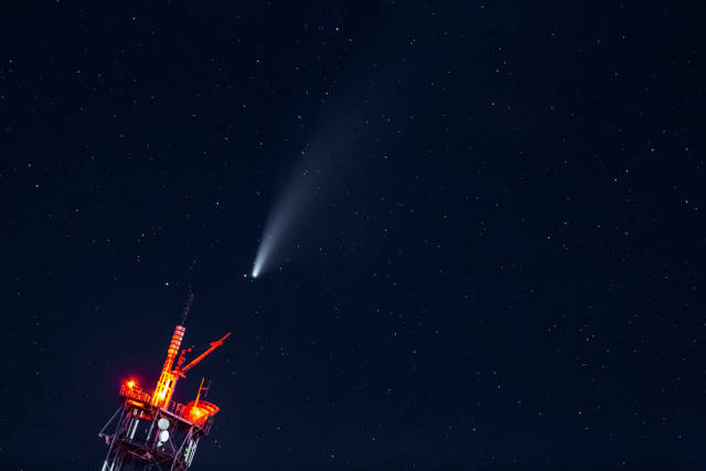Neowise Comet approaching the earth over a TV tower in the dark night sky with stars