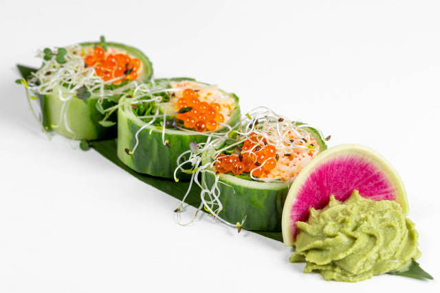 Fresh rolls with cucumber, avocado, crab, arugula and micro greens on a large green leaf with wasabi sauce