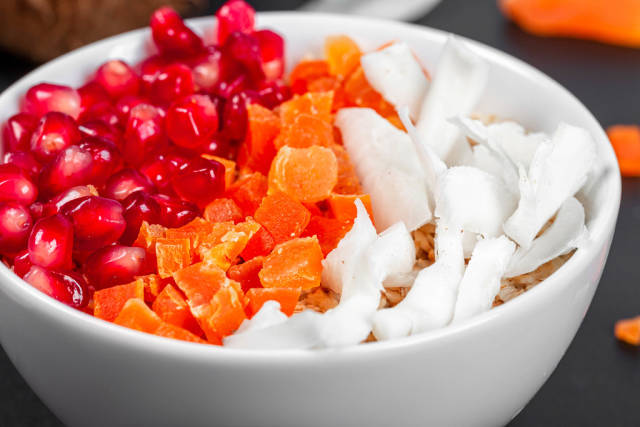 Close- up of oatmeal with coconut, dried apricots and pomegranate