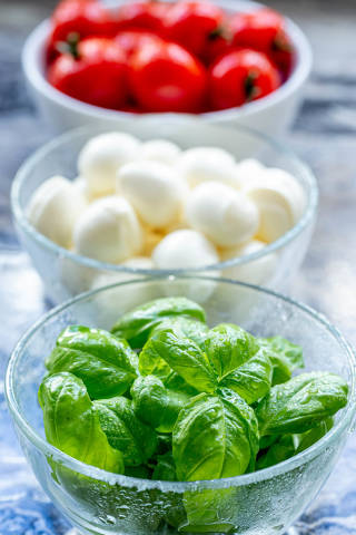 Close-up of Basil leaves and tomatoes with mozzarella behind