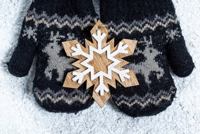 Childrens hands in mittens hold a wooden snowflake on a background of snow. Winter concept