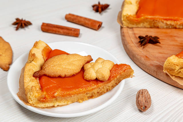 Close-up piece of pumpkin pie with cinnamon, anise stars and nutmeg