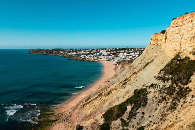 Küste mit steilen Klippen und weißem Dorf im Hintergrund bei Reserva da Luz, Portugal