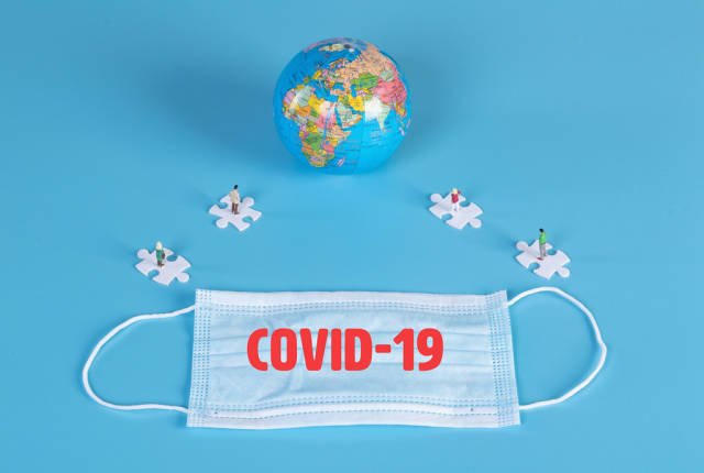 People standing on puzzle pieces, globe and medical face mask with Covid-19 text