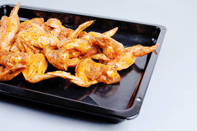 Raw chicken wings in pan, white background