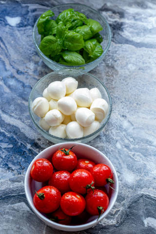 Ingredients for making Caprese salad on a grey background