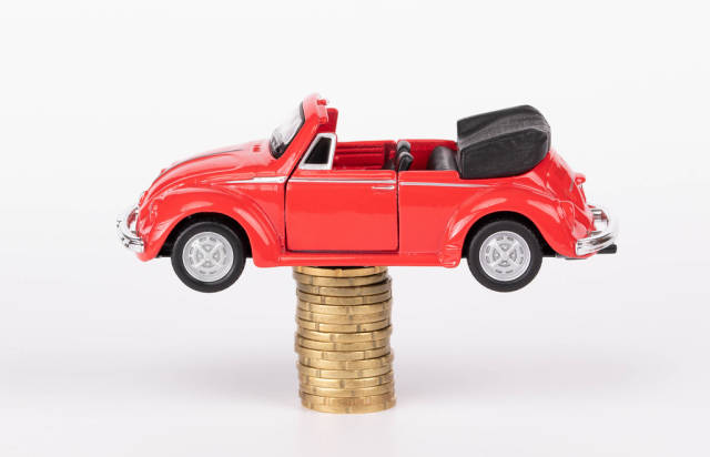 Red toy car on stack of coins