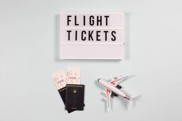 Flugscheine in Reisepässen und eine Leuchtbox mit den Worten Flight Tickets