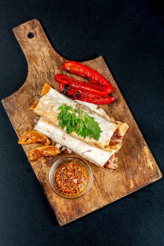 Top view, lula kebab in pita bread and grilled vegetables on an old wooden kitchen board