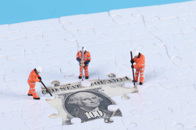 Group of workers with missing jigsaw puzzle pieces over money dollar background