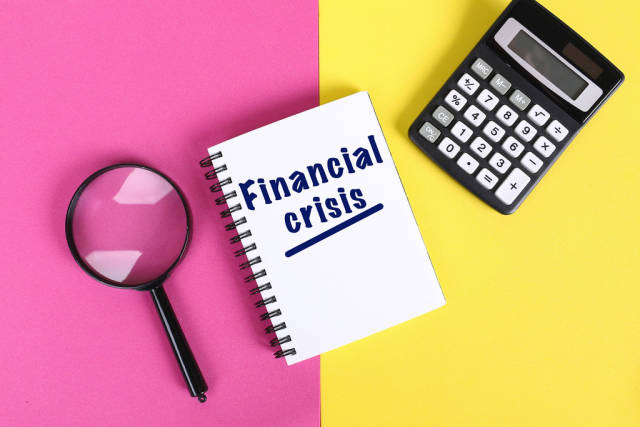 Financial crisis text in notebook on colorful background