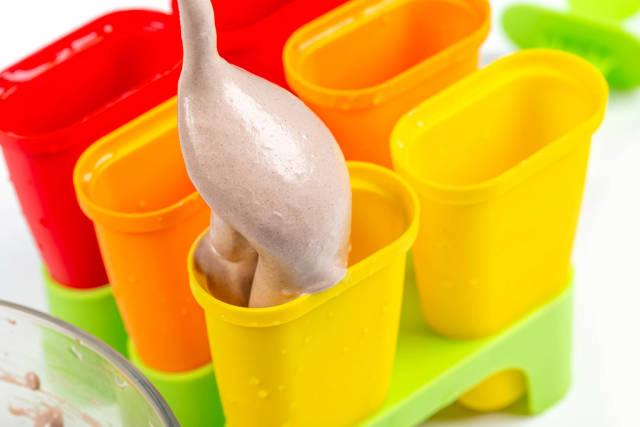 Pour a spoon of homemade ice cream into an ice cream mold