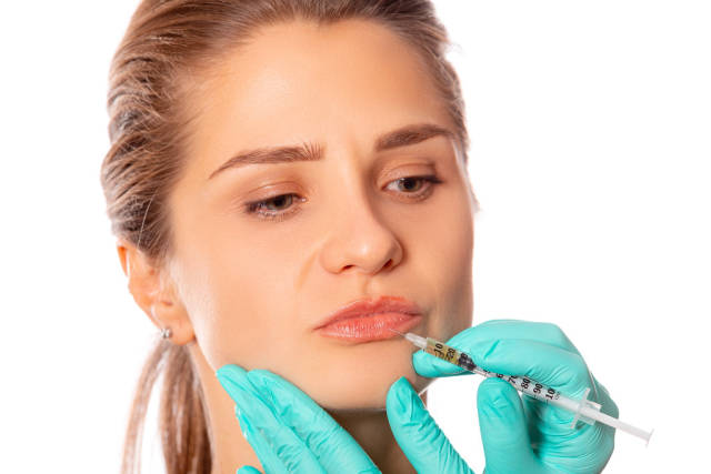 Close-up of a girls lips and a syringe for injection