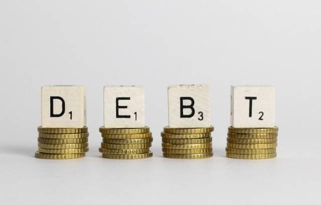 Dept: Englischer Begriff für Schulden als Scrabble-Würfel auf gestapelte Euro-Geldmünzen - frontale Nahansicht