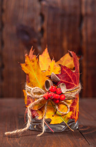 Original candle holder with autumn leaves and Rowan berries on wooden background