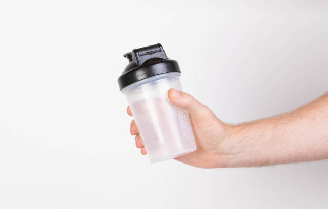 Hand holding empty protein shaker