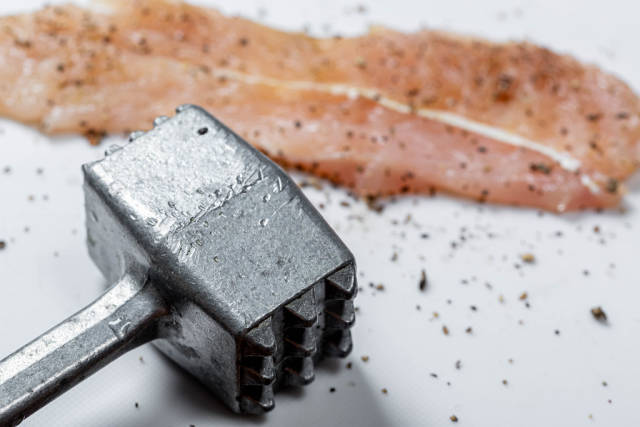 Closeup of iron hammer and a raw chop with spices. The concept of cooking