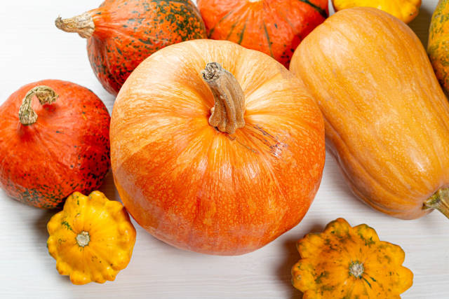 Ripe pumpkins on a white wooden background. Top view
