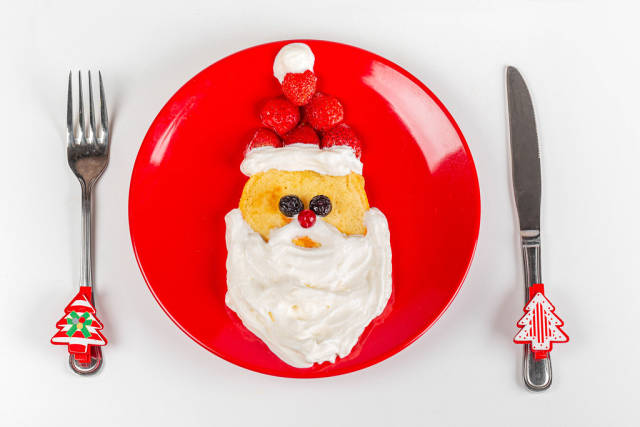 Top view of santa claus head made from pancakes, berries and whipped cream