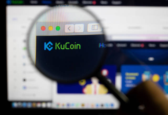 KuCoin logo on a computer screen with a magnifying glass