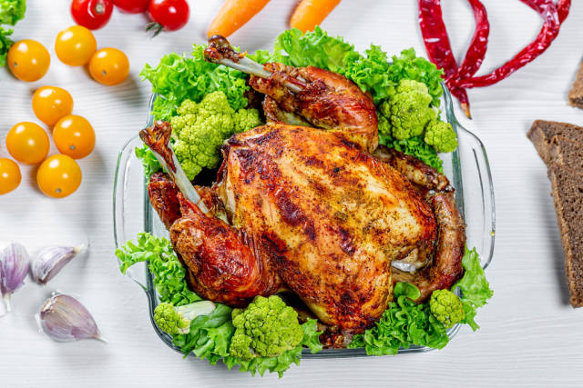Whole baked chicken with vegetables and spices.Top view