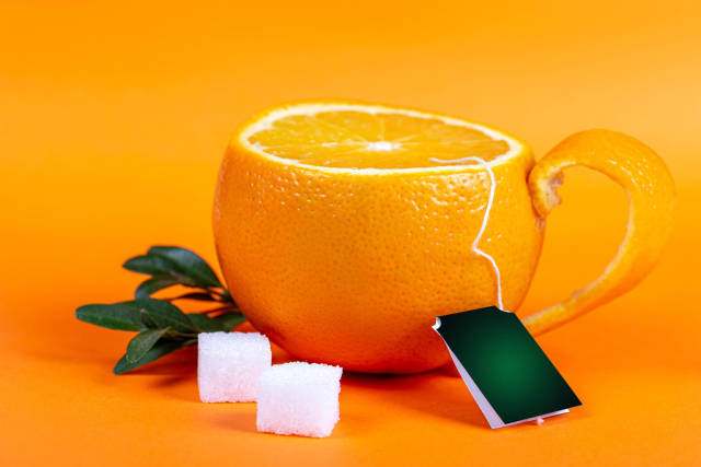 A cup made from fresh tangerine on an orange background with sugar cubes
