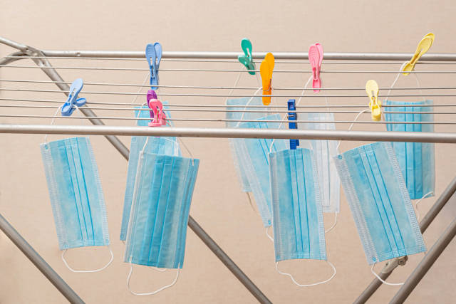Medical masks hang on a dryer with clothespins