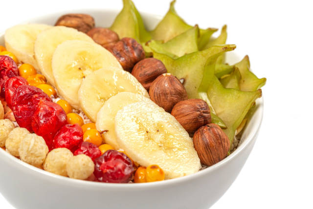 Oatmeal with slices of carom fruit, hazelnuts, banana, sea buckthorn and dried cherry, close-up