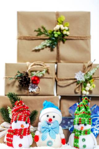 Three little Snowman with scarf and hat in front of stacked christmas presents
