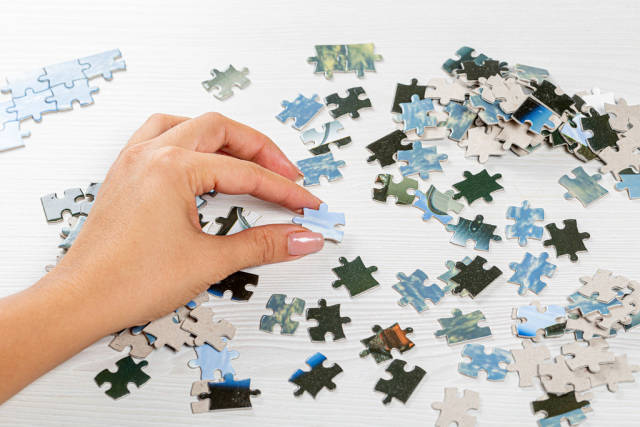 Lots of puzzle pieces on the table and one in a womans hand