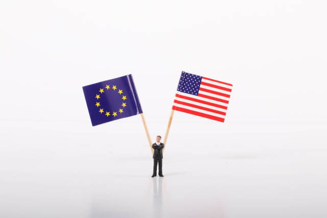 Businessman standing in front of flags of European Union and USA