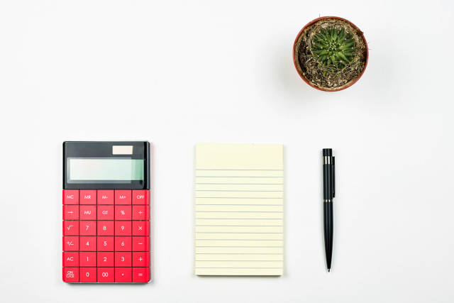Office desk table layout with calculator, notepad and cactus