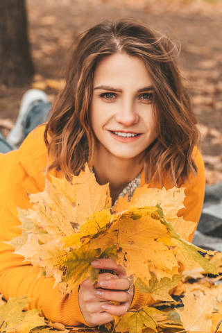 Portrait of a beautiful happy woman with a smile with an autumn yellow leaves in the park