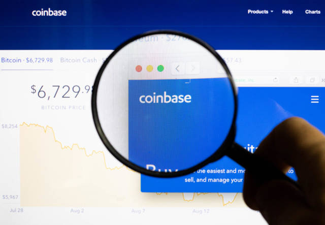 Man holding magnifying glass over Coinbase logo