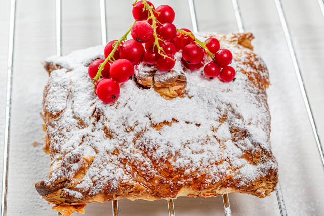 Sweet strudel with powdered sugar and a sprig of fresh red currant