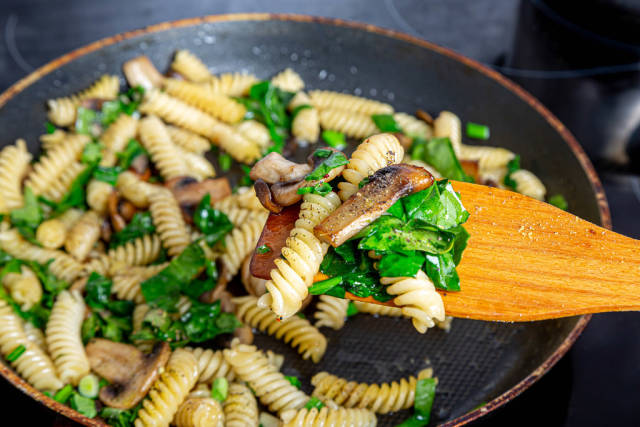 Close-up of pasta, mushrooms, herbs and spices on a wooden kitchen spatula