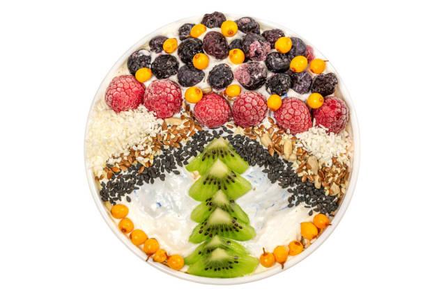 Oat flakes with sesame seeds, flax, sunflower, raspberries, blueberries, sea buckthorn and yogurt, top view