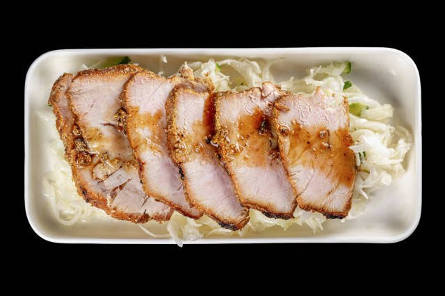 Sliced baked meat with cabbage salad with cucumber, top view