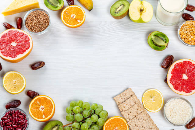Fresh fruits, cereals, milk, diet bread on a wooden white background with free space