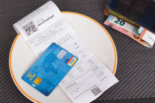 Restaurant bill, wallet and credit card on table
