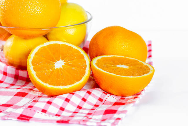 Vitamin C - A halfed orange with lemons and oranges in the background on a kitchen towel