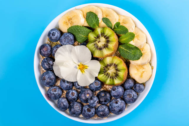 Top view, healthy breakfast, oatmeal with blueberry, banana, mint, kiwi and white flower on blue background