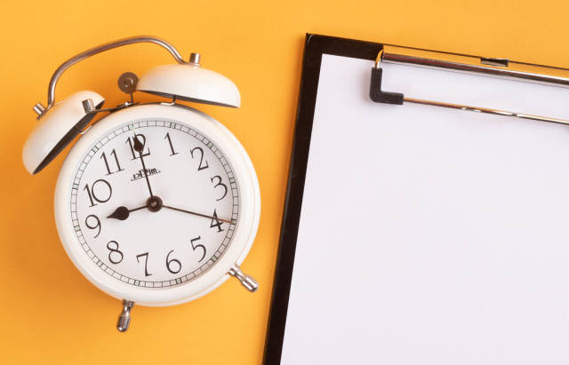 White alarm clock on yellow background with empty clipboard